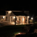Millcreek Landscape Design backyard outdoor patio and seating with landscaping at night time