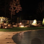 Millcreek Landscape Design hardscapes and landscaping around a inground pool at night time