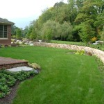 Millcreek Landscape Design stone wall surround home with planting and mulching design