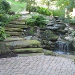Millcreek Landscaping Design backyard hardscape and landscaping with stone steps and waterfall in front of house