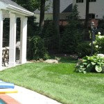Millcreek Landscape Design around an inground pool with plants and large rock