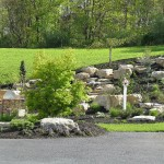Millcreek Landscape Design backyard oasis with stone patio, plants, trees and a pond