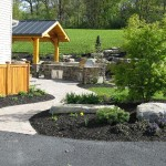 Millcreek Landscape Design backyard oasis with lard rocks and mulch