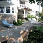 Millcreek Landscape Design backyard patio with beautiful trees, plants, and stone pathway