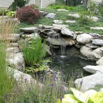 Millcreek Landscape Design backyard landscaping with a pond and large rocks