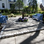 Millcreek Landscape Design backyard patio with two benches and flowers in the middle