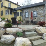stone paver patio area of yellow house