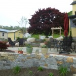 landscaping & stone retaining wall by yellow house