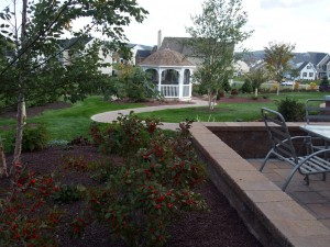 white gazebo surrounded by landscaped garden area