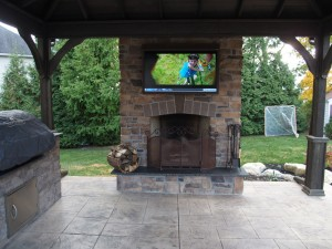 stone outdoor fire place with overhead television