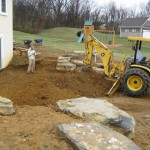 Millcreek Landscape Design worker and tractor digging up dirt in backyard