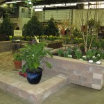 Millcreek Landscape Design pond with large rocks, waterfall, and yellow lilys