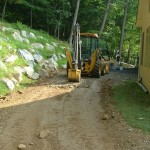 Millcreek Landscape Design work vehicle digging up dirt in residents backyard