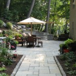 Millcreek Landscape Design stone patio with grill and fireplace