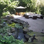 Millcreek Landscaping Design backyard hardscape patio design with outdoor kitchen, table, chairs, and plants