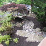 Millcreek Landscaping Design backyard hardscape and landscaping in front of house